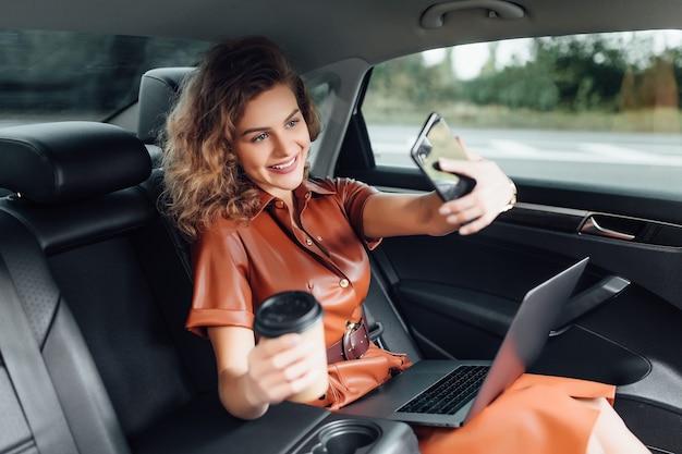 Jeune femme d'affaires attirante travaillant sur la voiture avec une tasse de café et tenant le téléphone tout en allant au travail