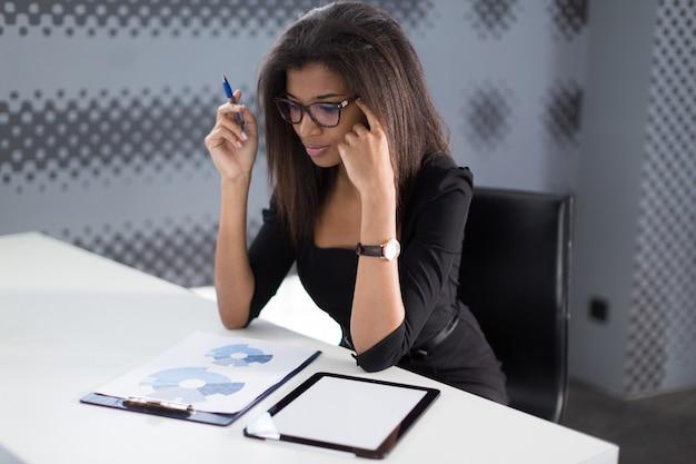 Jeune femme d'affaires attrayante dans une suite noire forte s'asseoir à la table de bureau