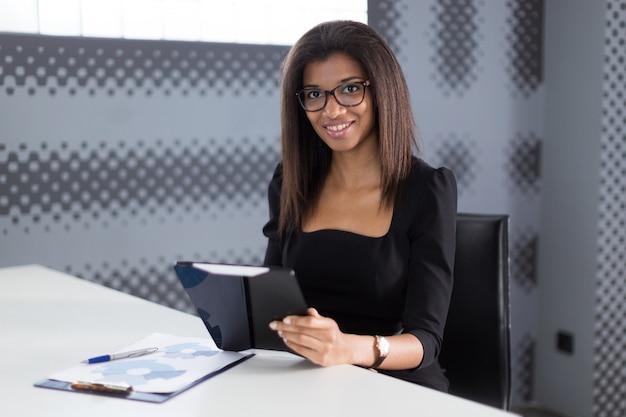Jeune femme d'affaires attrayante dans une suite noire solide assis à la table de bureau