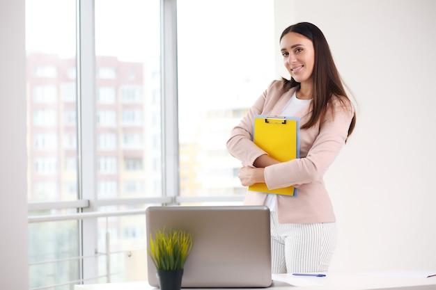 Jeune femme d'affaires attrayante tenant un cahier dans ses mains