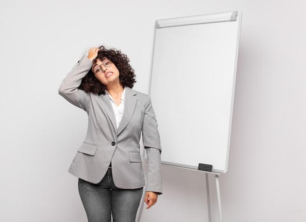 Jeune femme d'affaires aux cheveux bouclés et un tableau blanc