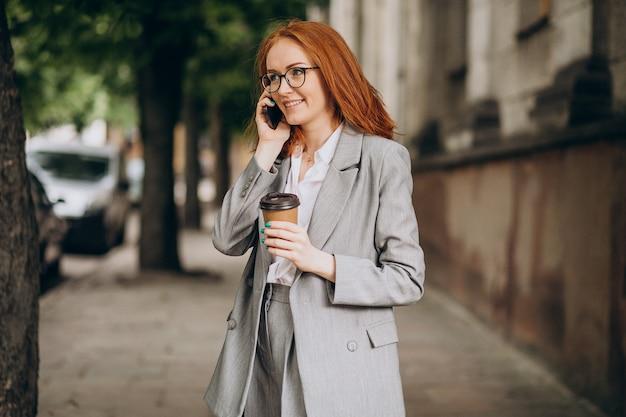 Jeune femme d'affaires aux cheveux rouges à l'aide de téléphone