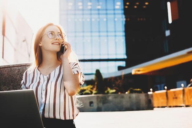 Jeune femme d'affaires aux cheveux rouges et taches de rousseur travaillant à son ordinateur portable à l'extérieur dans les escaliers