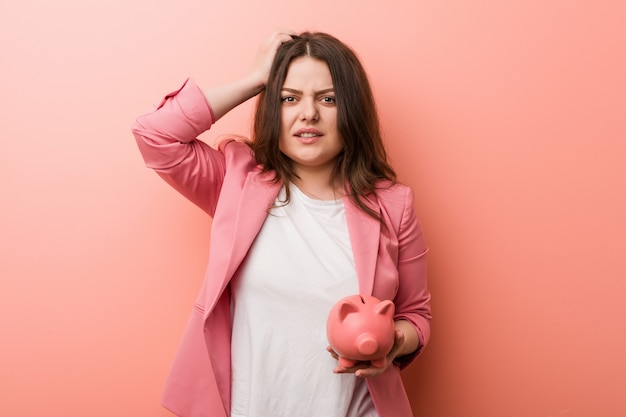 Jeune femme d'affaires aux courbes généreuses tenant une tirelire sous le choc, elle s'est souvenue d'une réunion importante.