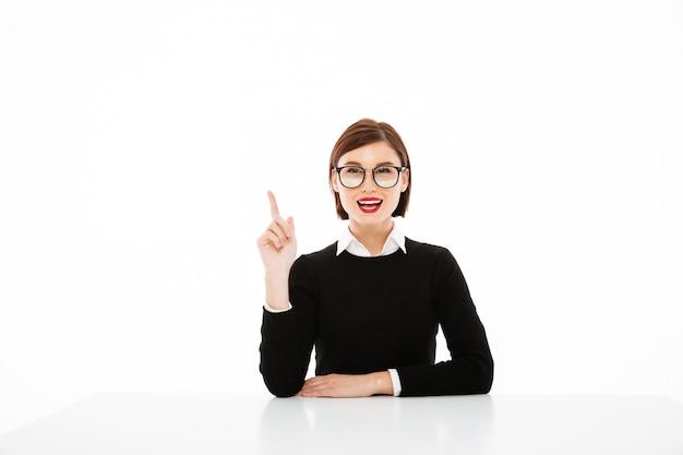 Jeune femme d'affaires ayant une idée, pointant vers le haut avec le doigt