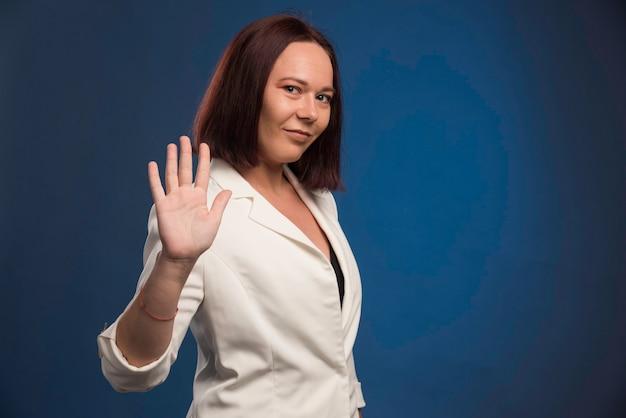 Jeune femme d'affaires en blazer blanc disant au revoir.