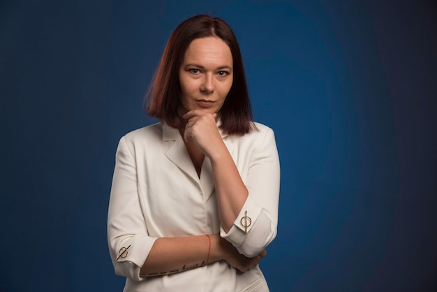 Jeune femme d'affaires en blazer blanc pensant.