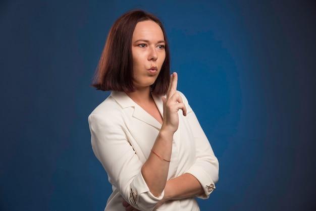 Jeune femme d'affaires en blazer blanc soufflant des armes à feu.
