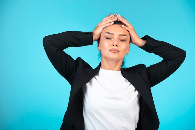 Jeune femme d'affaires en blazer noir ayant mal à la tête.