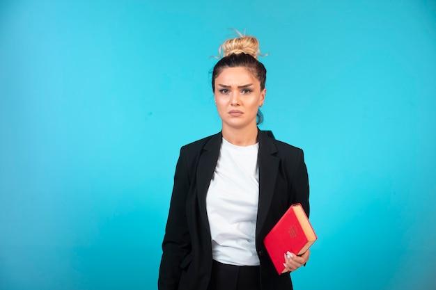 Jeune femme d'affaires en blazer noir tenant un livre et a l'air déprimé.
