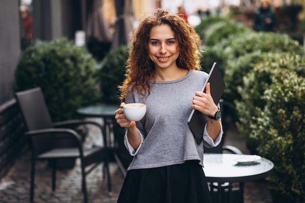 Jeune, femme affaires, boire café, dehors, café, tenue, ordinateur portable