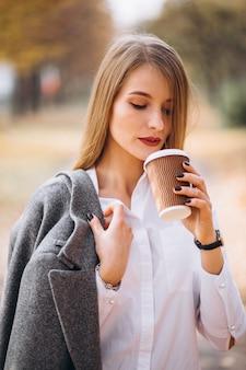 Jeune femme d'affaires boire un café en plein air