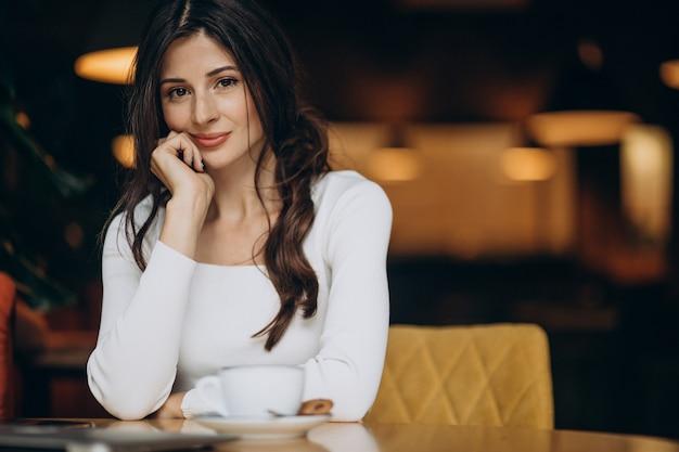 Jeune femme d'affaires, boire du café dans un café