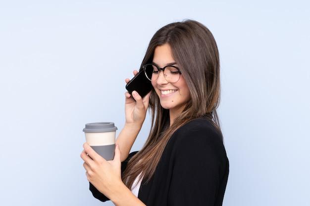 Jeune femme d'affaires brésilienne tenant un café à emporter et parler au mobile sur fond bleu isolé