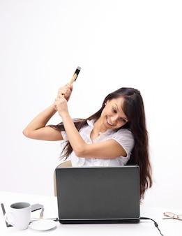 Jeune femme d'affaires brisant un ordinateur portable assis derrière un bureau