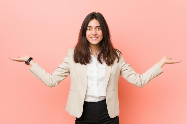 Jeune femme d'affaires brune fait l'échelle avec les bras, se sent heureuse et confiante
