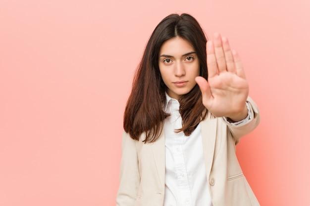 Jeune femme d'affaires brune sur un fond rose debout avec la main tendue montrant le panneau d'arrêt, vous empêchant.