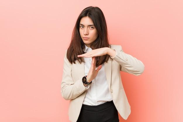 Jeune femme d'affaires brune montrant un geste de délai d'attente