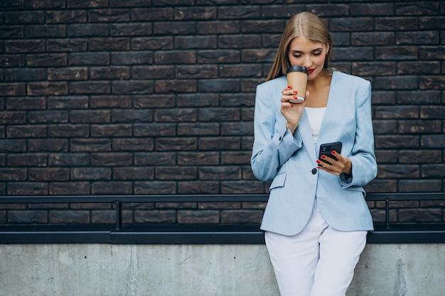 Jeune femme d'affaires buvant du café et parlant au téléphone