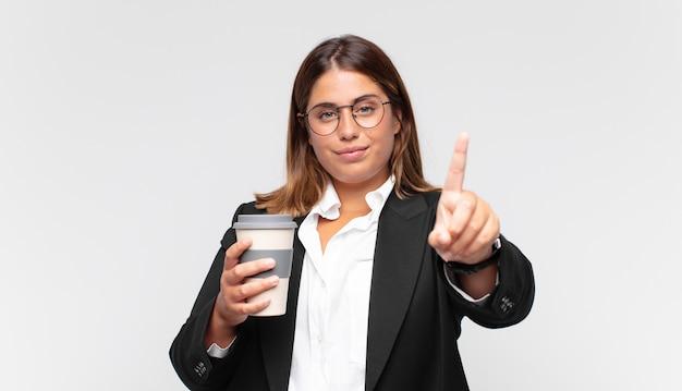 Jeune femme d'affaires avec un café souriant et à la convivialité, montrant le numéro un ou d'abord avec la main en avant, compte à rebours