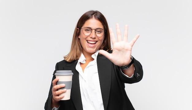 Jeune femme d'affaires avec un café souriant et à la convivialité, montrant le numéro cinq ou cinquième avec la main en avant, compte à rebours