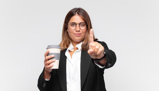 Jeune femme d'affaires avec un café souriant fièrement et en toute confiance faisant le numéro un pose triomphalement, se sentant comme un leader