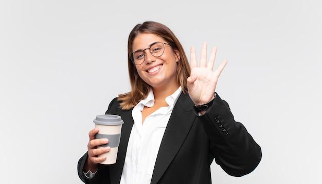 Jeune femme d'affaires avec un café souriant et à la sympathique, montrant le numéro quatre ou quatrième avec la main en avant, compte à rebours