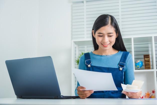 Jeune femme d'affaires calcul du budget familial, essayant d'économiser de l'argent avec une facture de papier financier.