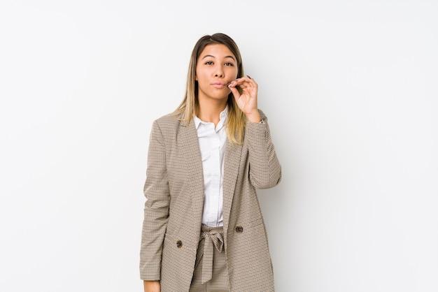 Jeune femme d'affaires caucasien isolée avec les doigts sur les lèvres en gardant un secret.