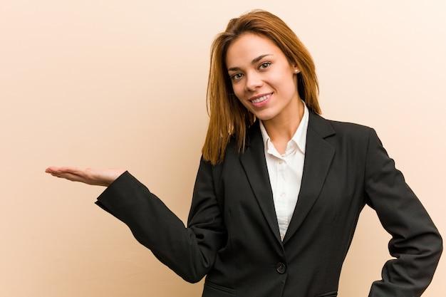 Jeune femme d'affaires caucasien montrant un espace de copie sur une paume et tenant une autre main sur la taille.