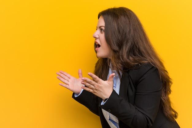 Jeune femme d'affaires caucasien de taille plus crie fort, garde les yeux ouverts et les mains tendues.