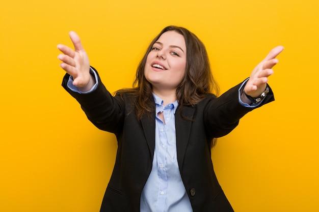 Jeune femme d'affaires caucasien taille plus se sent confiant en donnant un câlin à la caméra.