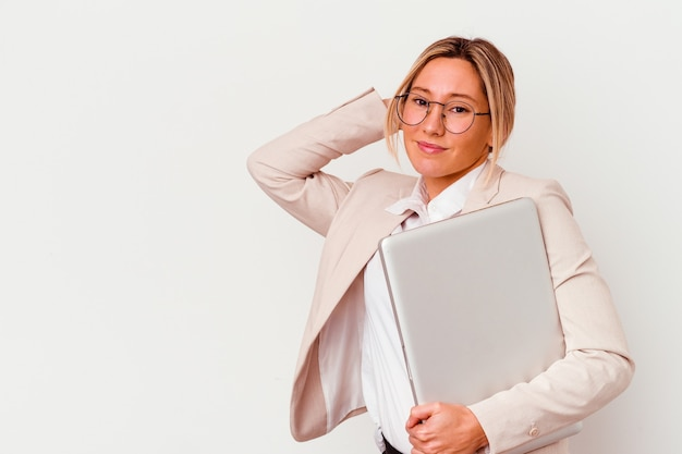 Jeune femme d'affaires caucasien tenant un ordinateur portable isolé sur fond blanc, toucher l'arrière de la tête, penser et faire un choix.