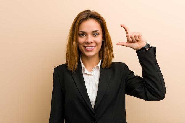 Jeune femme d'affaires caucasien tenant quelque chose de petit avec les index, souriant et confiant.