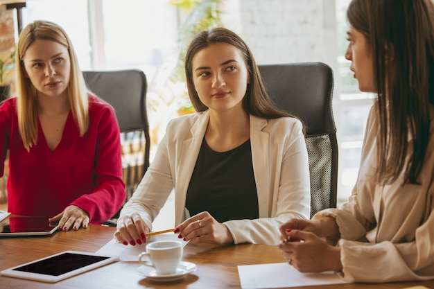 Jeune femme d'affaires caucasienne dans un bureau moderne avec équipe. réunion créative, attribution de tâches. les femmes travaillant au front-office. concept de finance, d'affaires, de pouvoir des filles, d'inclusion, de diversité, de féminisme.