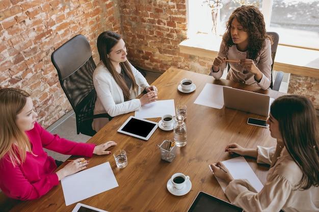 Jeune femme d'affaires caucasienne dans un bureau moderne avec équipe. réunion créative, attribution de tâches. les femmes travaillant au front-office. concept de finance, d'affaires, de pouvoir des filles, d'inclusion, de diversité. vue de dessus.