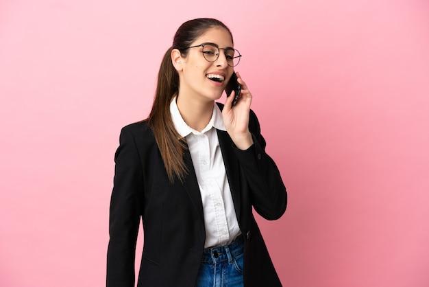 Jeune femme d'affaires caucasienne isolée sur fond rose en gardant une conversation avec le téléphone portable
