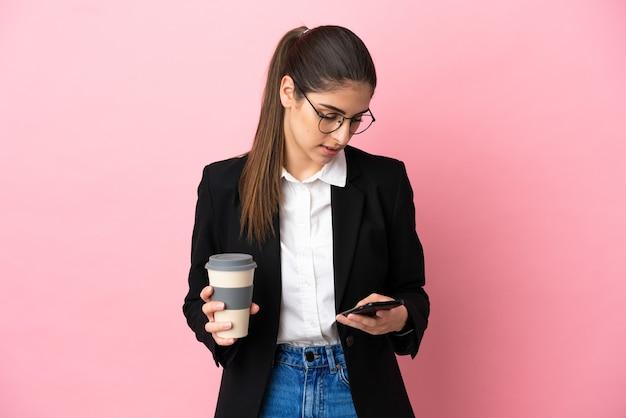 Jeune femme d'affaires caucasienne isolée sur fond rose tenant du café à emporter et un mobile