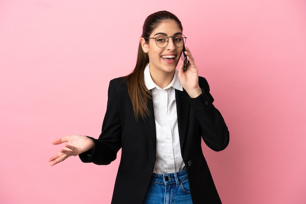 Jeune femme d'affaires caucasienne isolée sur un mur rose gardant une conversation avec le téléphone portable avec quelqu'un