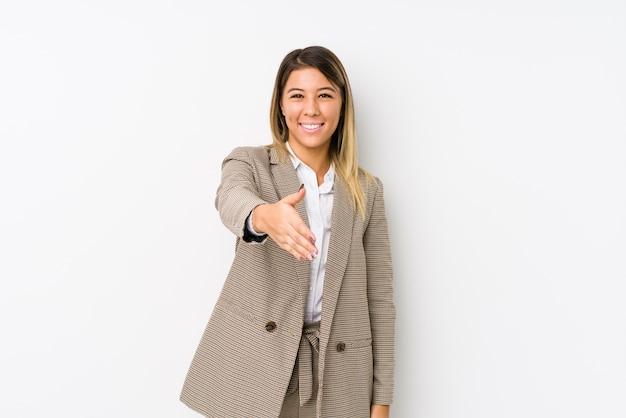 Jeune femme d'affaires caucasienne isolée qui s'étend de la main dans le geste de salutation.