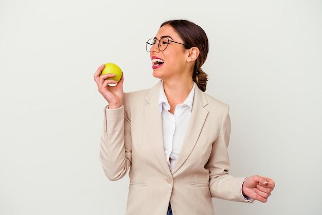 Jeune femme d'affaires caucasienne mangeant une pomme isolée