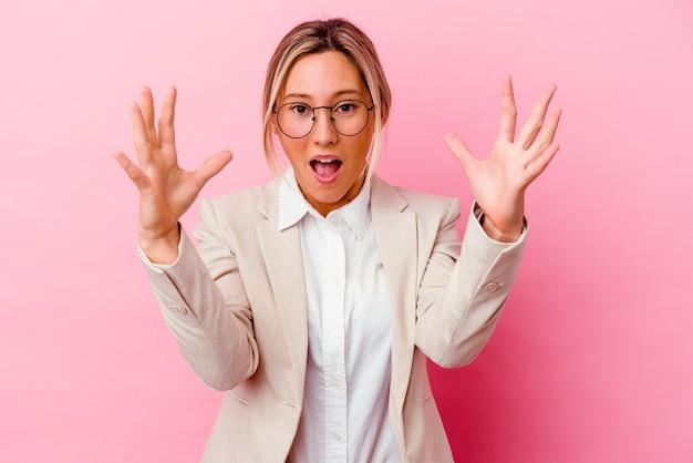 Jeune femme d'affaires caucasienne métisse isolée sur un mur rose recevant une agréable surprise, excitée et levant les mains.