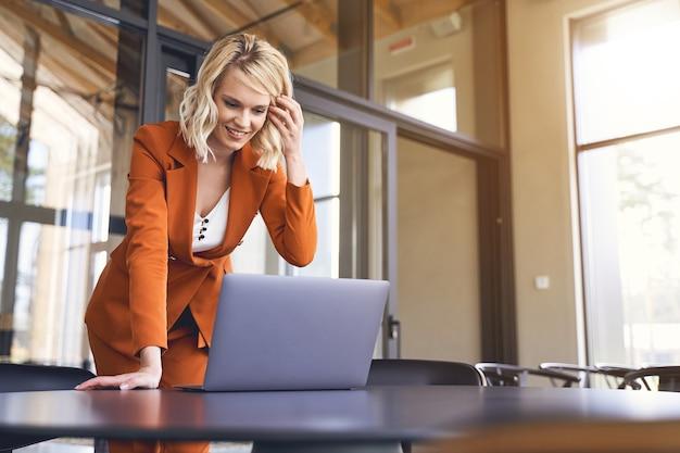 Jeune femme d'affaires caucasienne moderne et pleine d'entrain dans un tailleur-pantalon à la mode se penchant sur son ordinateur portable