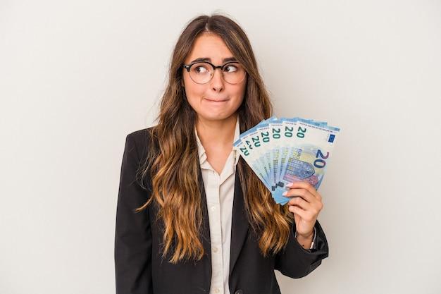 Jeune femme d'affaires caucasienne tenant des billets isolés sur fond blanc confus, se sent dubitative et incertaine.