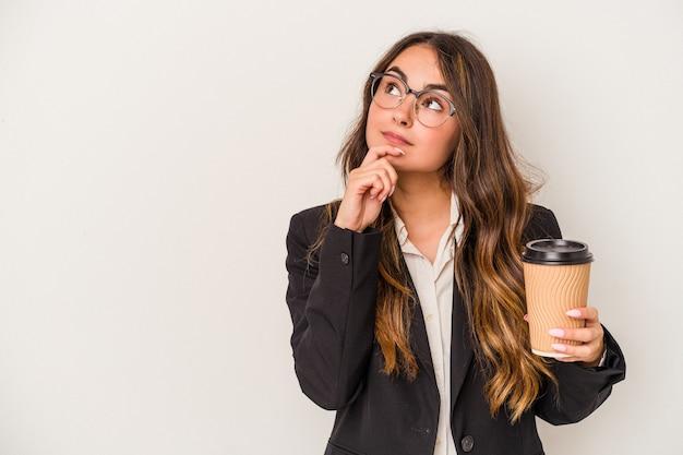 Jeune femme d'affaires caucasienne tenant un café à emporter isolé sur fond blanc regardant de côté avec une expression douteuse et sceptique.