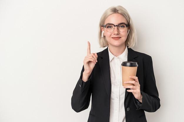 Jeune femme d'affaires caucasienne tenant du café à emporter isolé sur fond blanc montrant le numéro un avec le doigt.