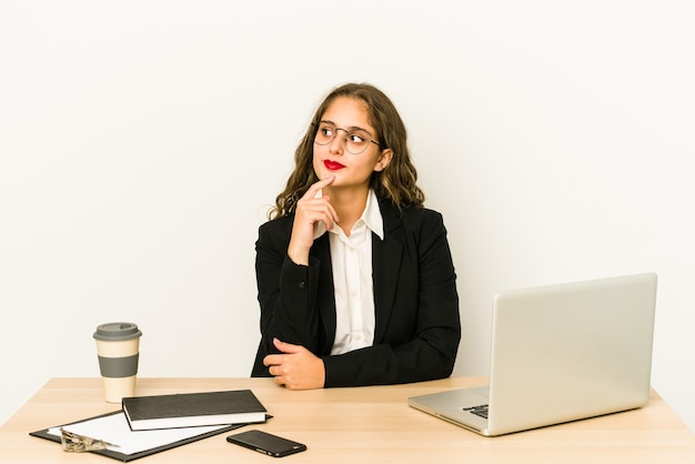 Jeune femme d'affaires caucasienne travaillant sur son bureau isolé à la recherche sur le côté avec une expression douteuse et sceptique.