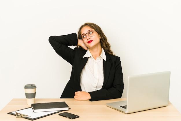 Jeune femme d'affaires caucasienne travaillant sur son bureau isolé toucher l'arrière de la tête, penser et faire un choix.