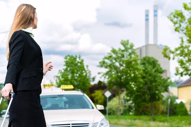 Jeune femme d'affaires avec chariot fait signe à un taxi de l'arrêter