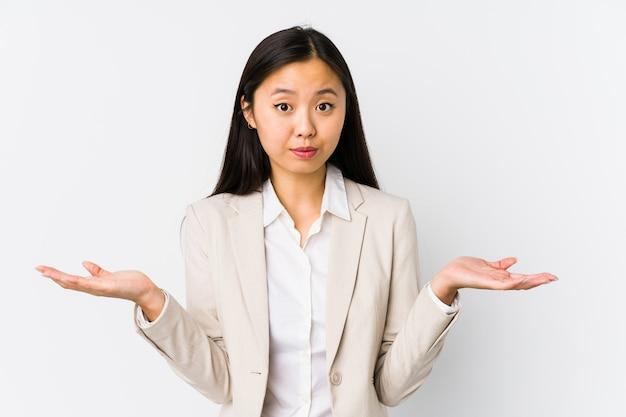Jeune femme d'affaires chinoise isolée doutant et haussant les épaules en remettant en question le geste.